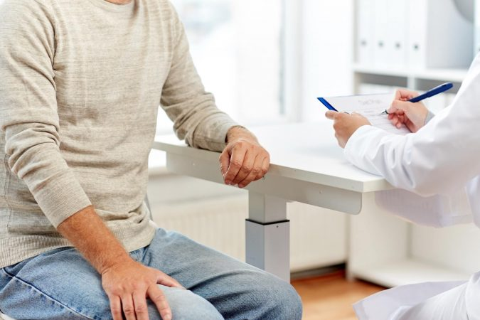 medicine, old age, healthcare and people concept - close up of senior man and doctor meeting in medical office at hospital
