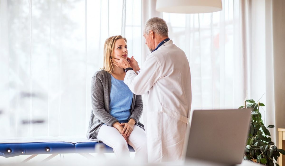 Senior doctor examining a young woman. A doctor and a patient at the doctors office.